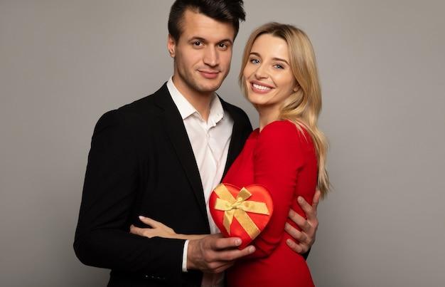 Close-up foto van een prachtig meisje in een rode jurk en aantrekkelijke man in een zwart pak, die knuffelen, in de camera kijken en glimlachen, terwijl ze een geschenkdoos vasthoudt.