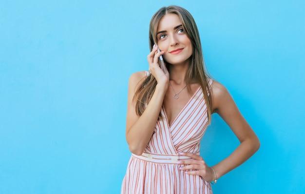 Close-up foto van een prachtig meisje met blond haar, naar links kijkend en glimlachend van vreugde terwijl ze aan de telefoon spreekt