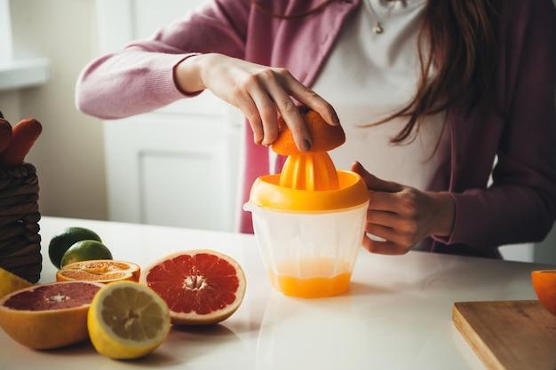 Close-up foto van een sinaasappelsap geperst met een pers door een blanke vrouw met gezonde gewoonten