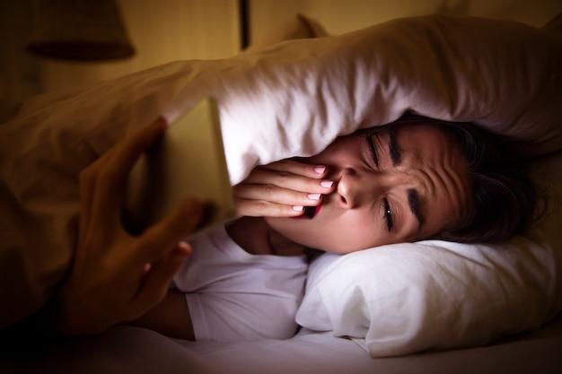 Close-up foto van een vermoeid meisje, liggend in haar bed onder de deken, die moeite heeft met slapen vanwege haar internetverslaving.