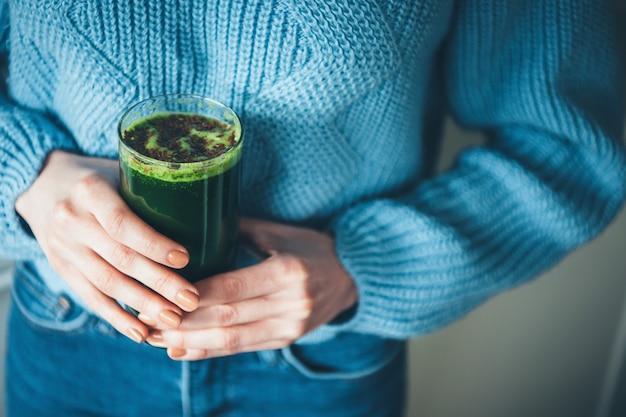 Close-up foto van een vers groen sap gehouden door vrouw in gebreide trui