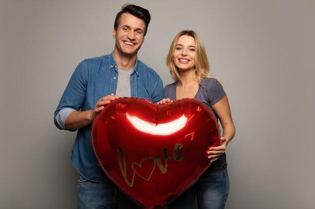 Close-up foto van een vrolijk stel in vrijetijdskleding, die een grote hartvormige ballon bij elkaar houden, glimlachen en elkaar in de ogen kijken.