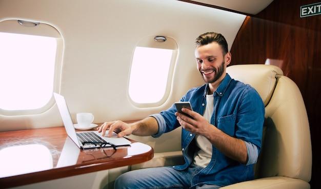 Close-up foto van een vrolijke man in een casual outfit, die geniet van zijn vlucht, op zijn stoel bij het raam zit en berichten uitwisselt op zijn smartphone.