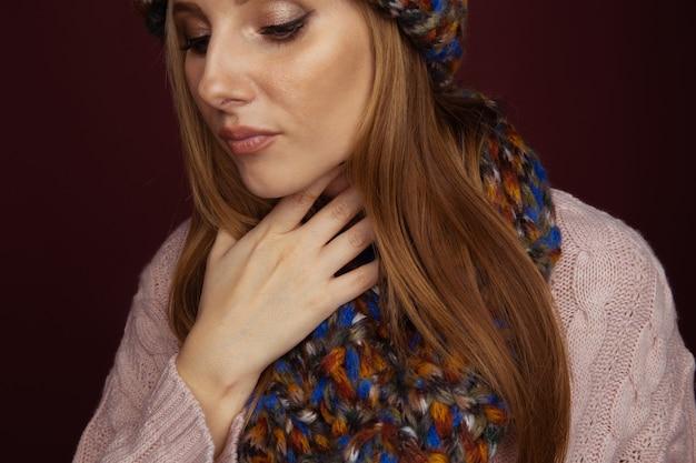 Close-up foto van een vrouw in de winterkleren die haar keel vasthoudt en pijn erin voelt.