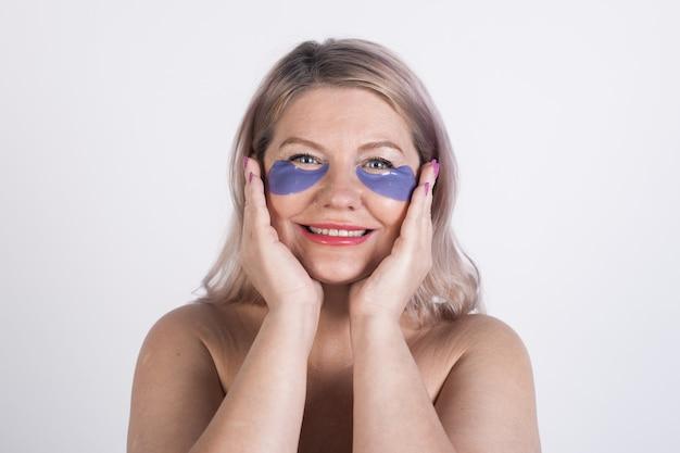 Close-up foto van een vrouw met ooglapjes van hydrogel en lach naar de camera met blote schouders op een witte studiomuur