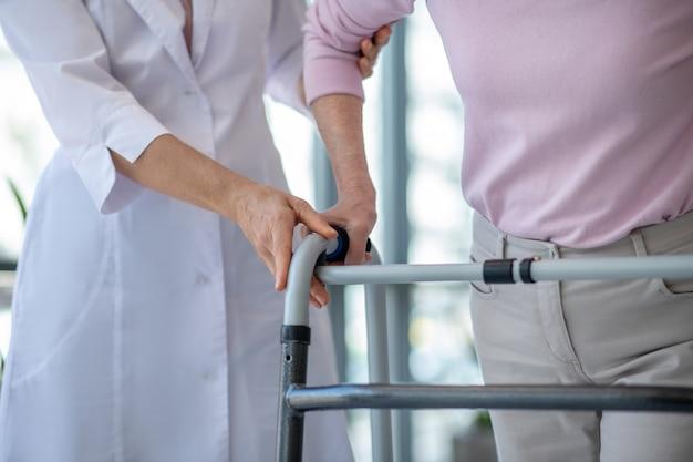 Close-up foto van een vrouw met rollator en een dokter
