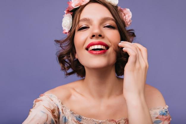 Close-up foto van enthousiaste jonge vrouw lachen. goedgehumeurd vrouwelijk model in een bloemencirkel.