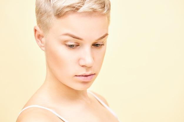 Close-up foto van ernstige doordachte jonge blonde vrouw met stijlvol kort kapsel met peinzende gezichtsuitdrukking. leuk mooi meisje met perfecte pure huid poseren geïsoleerd, naar beneden te kijken