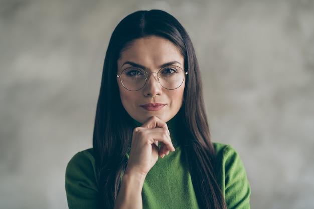 Close-up foto van ernstige zelfverzekerde slimme vrouw haar kin aanraken met hand dragen bril bril dragen geïsoleerde grijze kleur muur betonnen achtergrond
