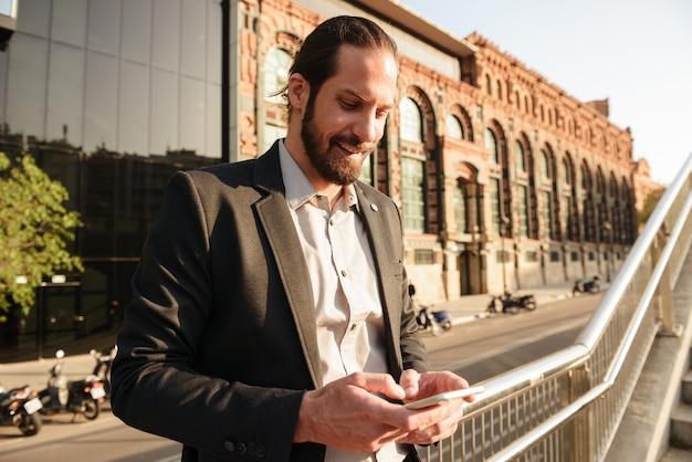 Close-up foto van europese knappe man 30s in formeel pak met behulp van smartphone, terwijl staande voor kantoorgebouw of zakencentrum