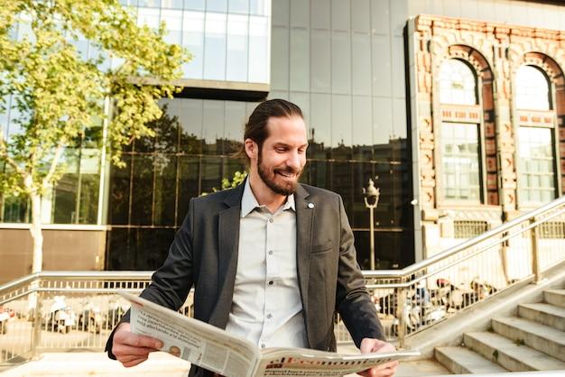 Close-up foto van europese knappe man 30s in formeel pak, staande voor kantoorgebouw of zakencentrum en krant lezen over economie
