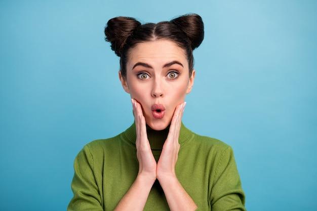 Close-up foto van funky aantrekkelijke dame tiener twee mooie broodjes open mond luisteren geweldig nieuws armen op wangen dragen warme groene coltrui geïsoleerde blauwe kleur muur