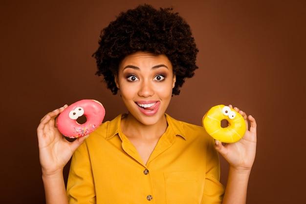 Close-up foto van funky donkere huid dame houdt twee kleurrijke donuts karamel ogen menselijke gezichten schilderij hongerige likken lippen dragen geel shirt geïsoleerde bruine kleur