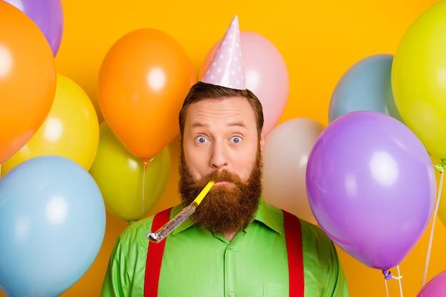 Close-up foto van funky grappige zorgeloze man blazen partij fluitje hebben lucht helium ballen baloons dragen goed uitziende kleding over felle kleuren