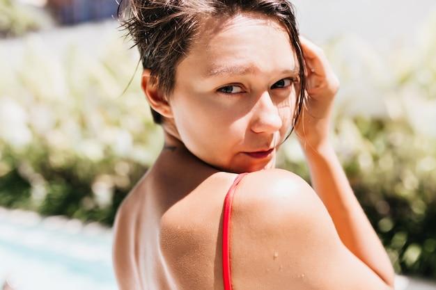 Close-up foto van geïnspireerde gebruinde vrouw die over schouder kijkt.