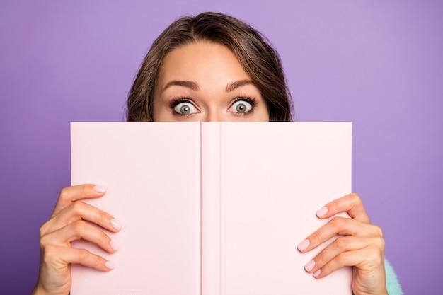 Close-up foto van gekke mooie dame houdt planner voorbeeldenboek verbergen half gezichtsuitdrukking verlegen persoon grote ogen dragen trui geïsoleerde paarse kleur