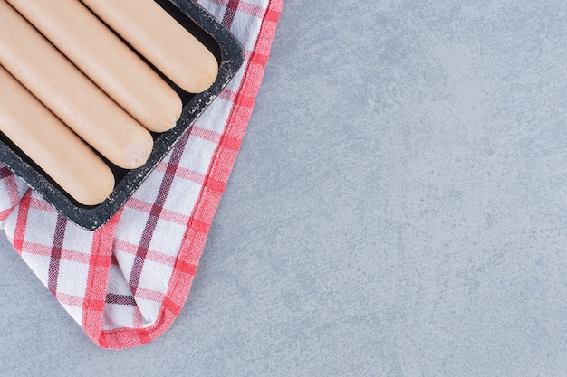 Close-up foto van gekookte worst op zwarte houten bord.