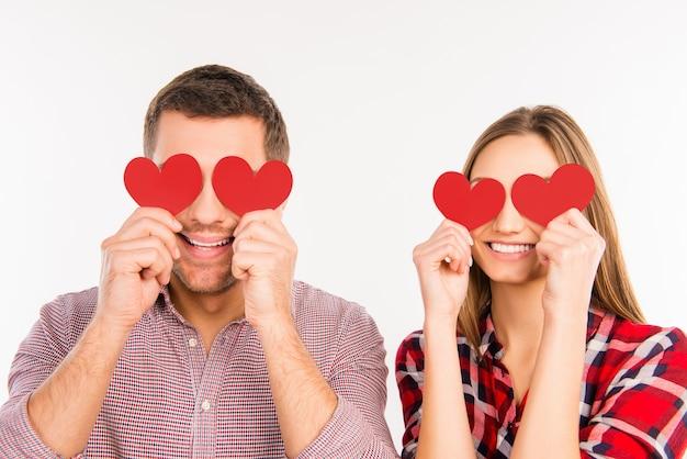 Close-up foto van gelukkige paar verliefd ogen verbergen achter papieren harten