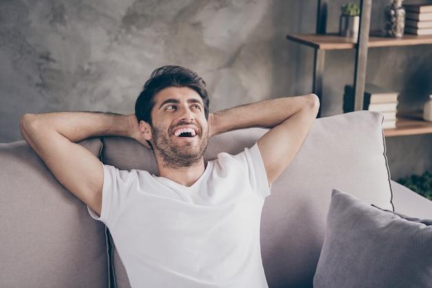 Close-up foto van gemengd ras man zitten gezellige bank hand in hand achter hoofd ontspannen huiselijke weekend stemming op zoek dromerige kant dragen casual outfit platte woonkamer binnenshuis