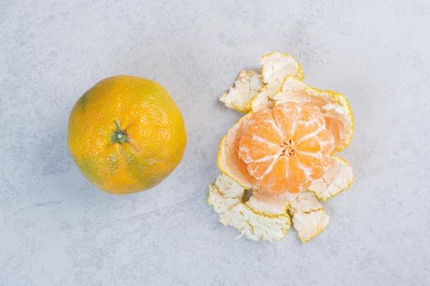 Close-up foto van gepelde en hele mandarijn.