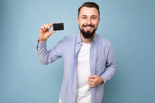 Close-up foto van goed uitziende cool lachende brunette bebaarde jonge man dragen stijlvol blauw shirt en wit t-shirt geïsoleerd over blauwe achtergrond muur met creditcard camera kijken