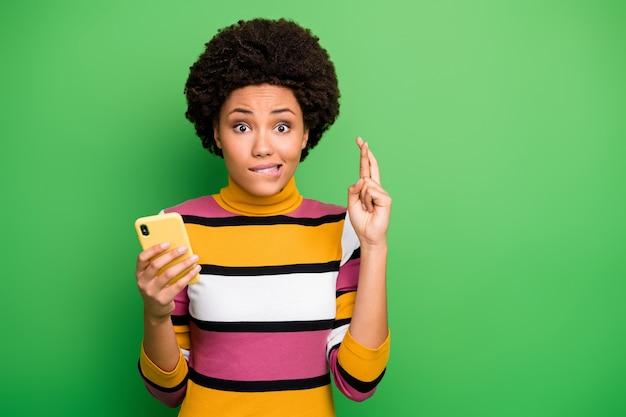 Close-up foto van grappige donkere huid golvende dame houden telefoon vingers gekruist wachten opstarten investeringsresultaten bijten lippen bezorgd dragen casual gestreepte trui