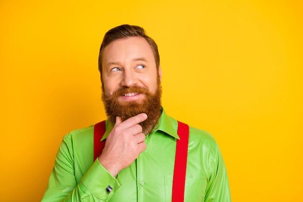 Close-up foto van grappige roodharige man kijken kant lege ruimte denken over gekke truc arm op kin dragen groen shirt rode bretels geïsoleerde levendige kleuren