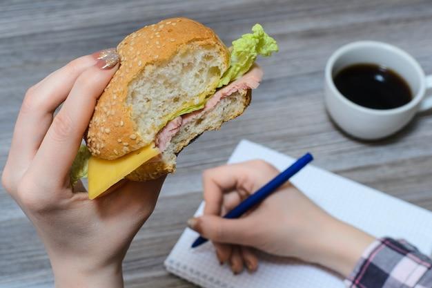 Close-up foto van handen met gebeten hamburger en pen over voorbeeldenboek kopje houten tafel achtergrond
