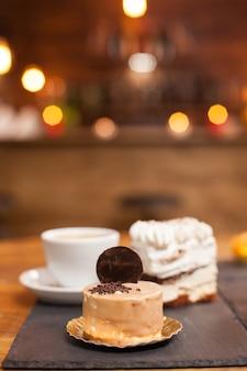 Close-up foto van heerlijke chocoladetaart met lekker koekje bovenop. lekkere minicakes in een koffieshop. traditionele desserts.