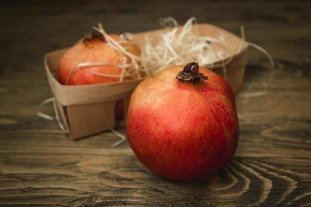 Close-up foto van hele granaatappel liggend op oud houten bureau