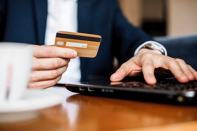 Close-up foto van iemands handen met behulp van creditcard en iets te koop kopen.