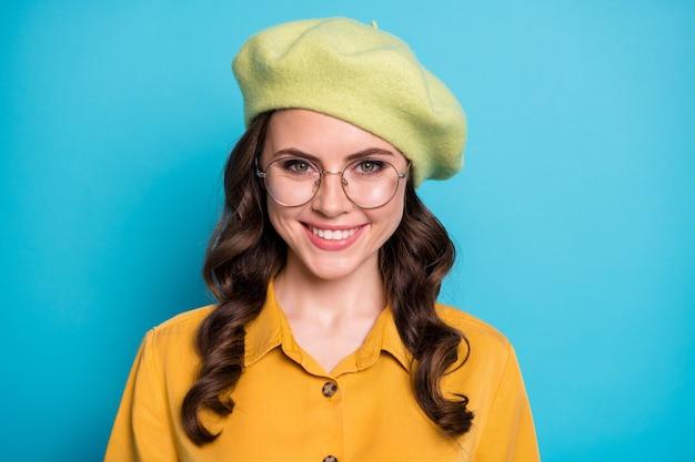 Close-up foto van inhoud openhartig meisje ziet er goed uit, brede glimlach in de camera geniet van rust, ontspannen geïsoleerd over blauwe kleur achtergrond