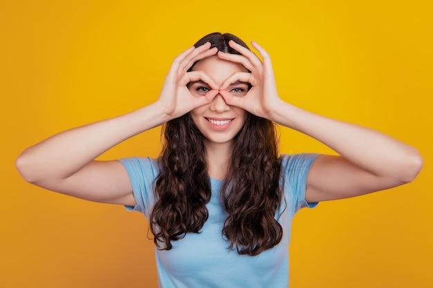 Close-up foto van jong vrolijk meisje gelukkig positieve glimlach toon oke teken geïsoleerde gele achtergrond