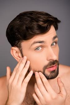 Close-up foto van jonge aantrekkelijke man kijkt naar zijn gezicht