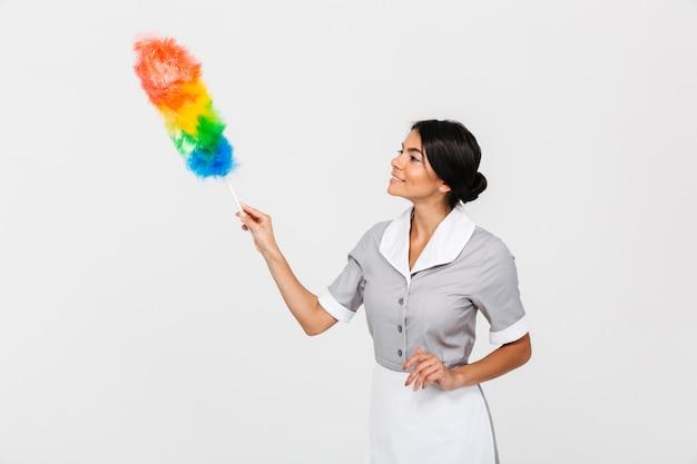 Close-up foto van jonge vrolijke huishoudster in uniform schoonmaken met stofdoek, opzij kijken