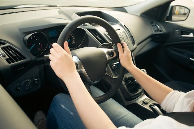Close-up foto van jonge vrouw die auto rijdt en op de weg kijkt