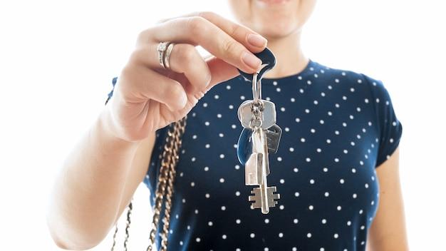 Close-up foto van jonge vrouw die sleutels van een nieuw huis vasthoudt en laat zien