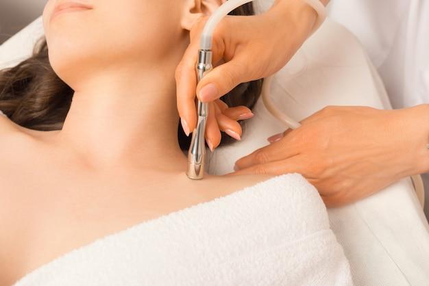 Close-up foto van jonge vrouw met huidbehandeling met vacuüm bij schoonheidsspecialist