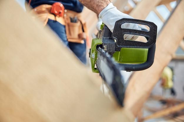 Close-up foto van kettingzaag in handen van bekwame bouwer die bouwhout snijdt voor het bouwen van een dak