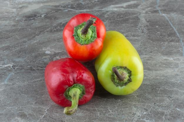 Close-up foto van kleurrijke paprika's op grijze achtergrond.