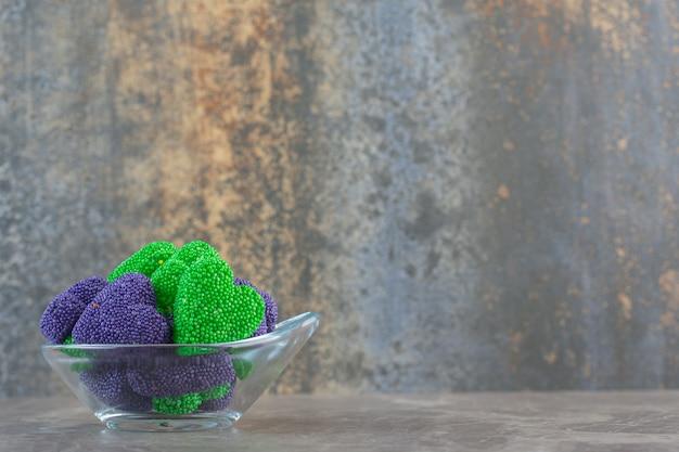 Close-up foto van kleurrijke snoepjes in glazen kom over grijze achtergrond.