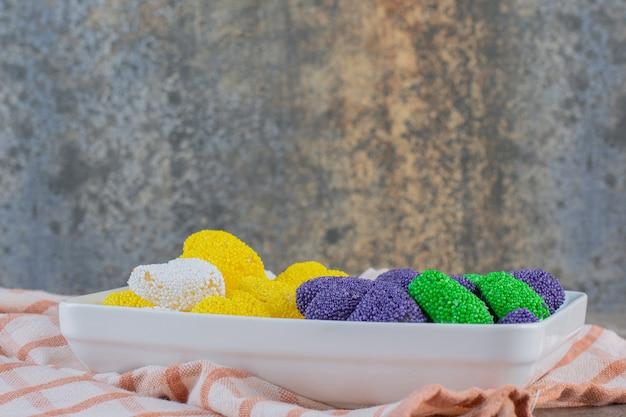 Close-up foto van kleurrijke zoete gelei op witte plaat. paars groen en geel.