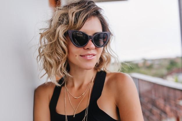 Close-up foto van knappe blonde vrouw in zwarte zonnebril. buiten schot van blonde vrouwelijke model genieten van een goede warme dag.