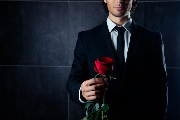 Close-up foto van knappe jonge man in formalwear met rode roos