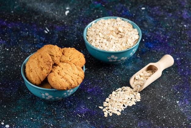 Close-up foto van koekjes en havermout in kom over donkere tafel.