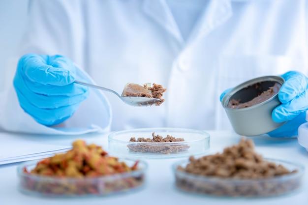 Close-up foto van kwaliteitscontrolepersoneel inspecteert de kwaliteit van ingeblikt voedsel voor huisdieren. fysieke kwaliteitscontrole. kwaliteitscontroleproces van de huisdiervoedingsindustrie.