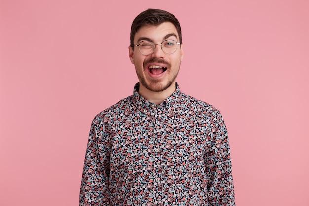 Close-up foto van lieve, hartverscheurende donkerharige aantrekkelijke man in glazen, flirten met iemand, knipoogt met goedkeuring voorbestemd interes, in coloful shirt, geïsoleerd op roze studio achtergrond