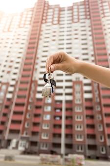 Close-up foto van makelaar in onroerend goed met sleutels van nieuw huis