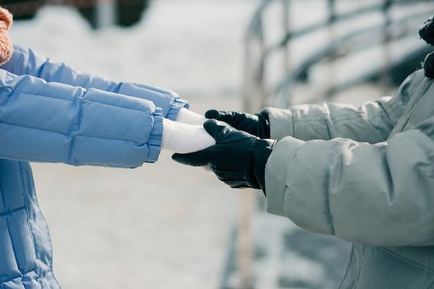 Close-up foto van man en vrouw in winterjassen en handschoenen hand in hand