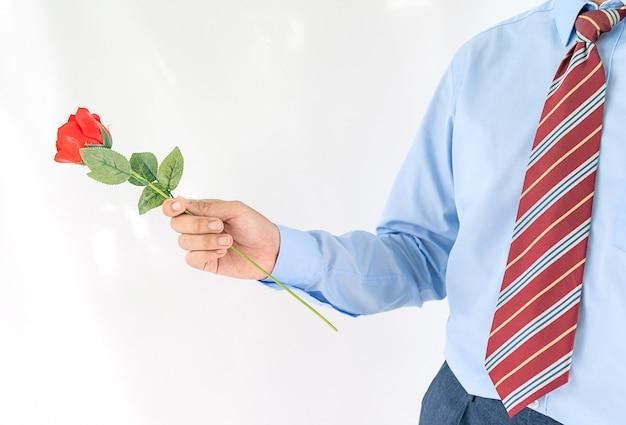 Close-up foto van man met rode roos op witte achtergrond Premium Foto